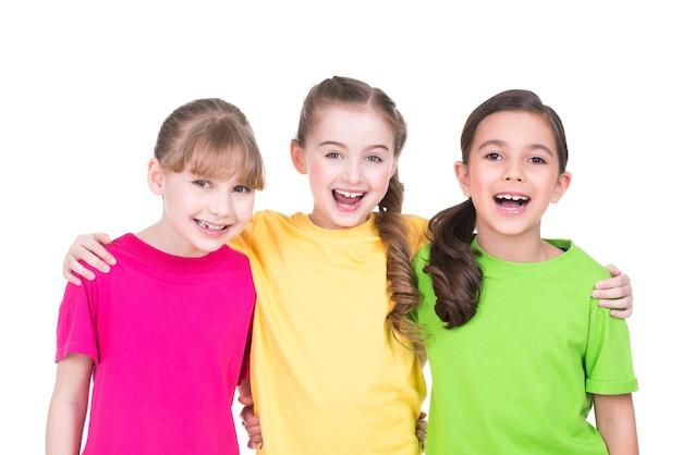 Drie schattige kleine schattige lachende meisjes in kleurrijke t-shirts staan - geïsoleerd op wit.