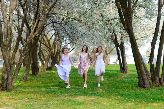 Drie schattige meisjes in jurken houden handen in een cirkel, hand in hand. lente, tuin.