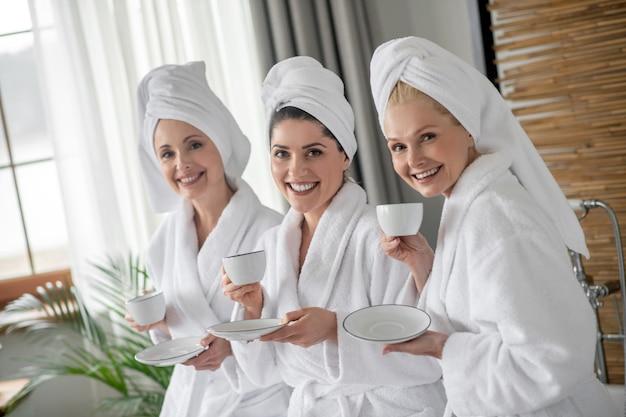 Drie schattige volwassen vriendinnen in spa