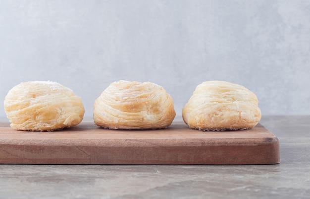 Drie schilferige koekjes op een bord op een marmeren oppervlak