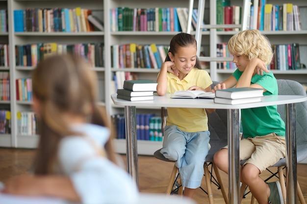 Drie schoolkinderen zitten aan bureaus in een openbare bibliotheek