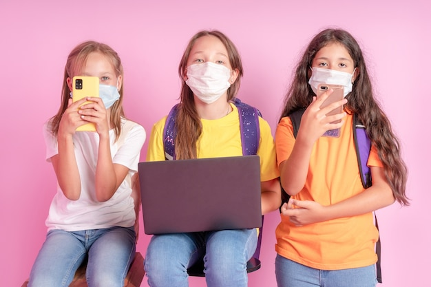 Drie schoolmeisjes in medische maskers met telefoons en een laptop in hun handen kijken naar de camera op een roze achtergrond.