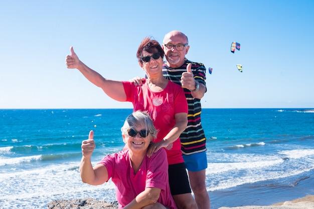 Drie senior mensen in vriendschap op de klif. lach en geluk buiten. blauwe lucht en oceaan met golven. paradijs voor windsurf- of kitesurfliefhebbers