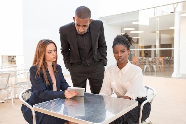Drie serieuze jonge collega's met discussie bij café