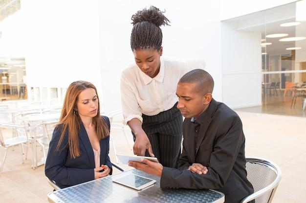 Drie serieuze partners kijken naar presentatie op digitale tablet