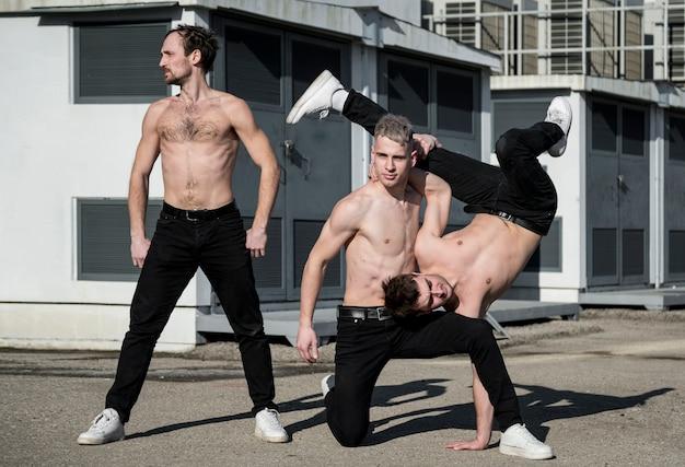 Drie shirtless hiphop poseren buiten tijdens het dansen
