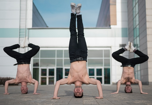 Drie shirtless hiphopartiesten die buiten oefenen