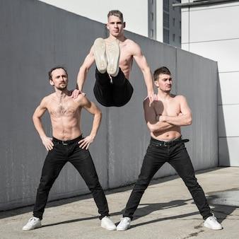 Drie shirtless hiphopartiesten die samen buiten stellen