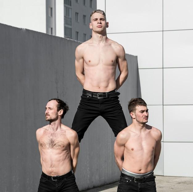 Drie shirtless hiphopartiesten poseren voor het dansen