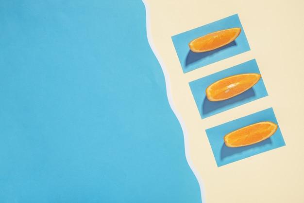 Drie sinaasappelschijfjes zonnebaden op het strand bij de zee