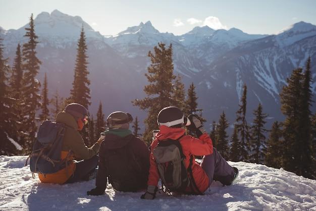 Drie skiërs die op met sneeuw bedekte berg ontspannen