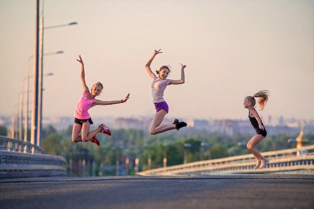 Drie slanke sportmeisjes springen op de weg op een zomeravond tegen de achtergrond van het panorama van de stad en de roze avondrood