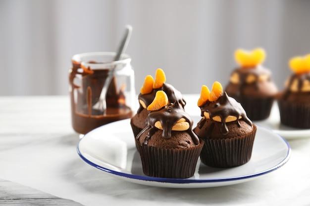 Drie smakelijke cupcakes met schijfje mandarijn en chocolade op een bord, close-up