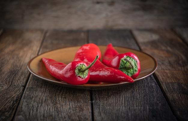 Drie smakelijke rode paprika's in een keramische plaat op een houten keukentafel