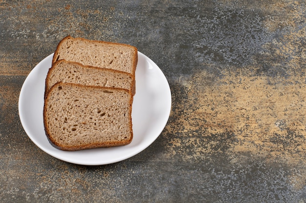 Drie sneetjes zwart brood op een witte plaat.