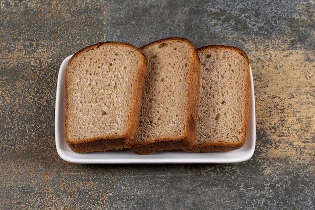 Drie sneetjes zwart brood op witte vierkante plaat