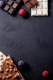 Drie soorten chocolade zwart, melk en wit met luxe handgemaakte chocolaatjes op een zwarte