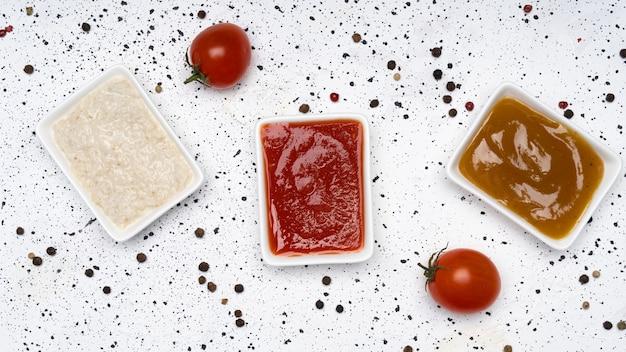 Drie soorten sauzen op een witte cementachtergrond