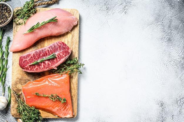Drie soorten steaks. rundermesje, zalmfilet en kalkoenfilet. biologische vis, gevogelte en rundvlees op grijs. bovenaanzicht. kopieer ruimte