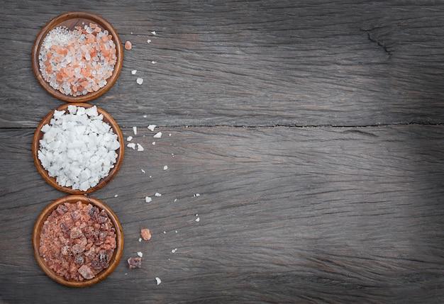 Drie soorten zout in houten kommen op een houten achtergrond
