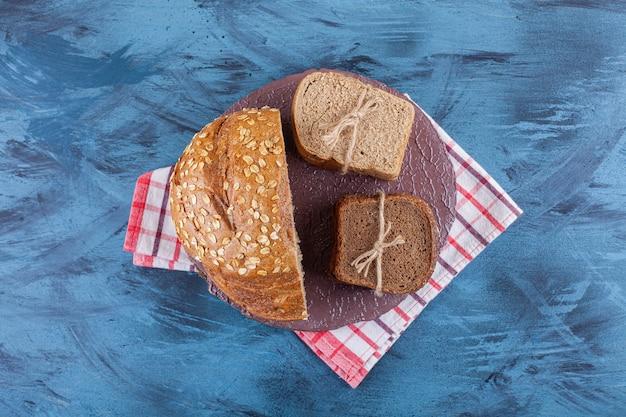 Drie soorten zwart vers brood op paarse plaat.