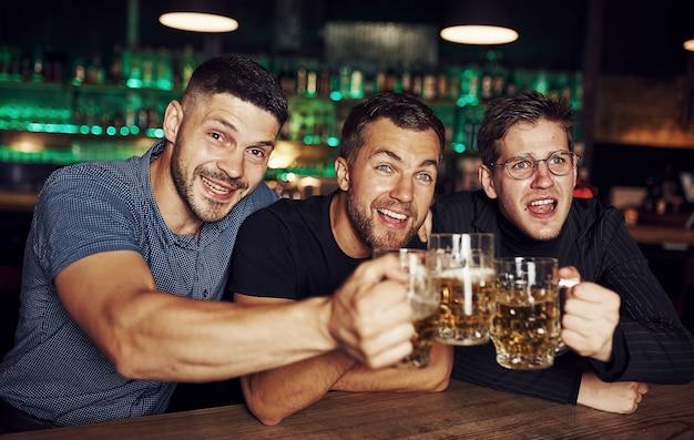 Drie sportfans in een bar voetbal kijken