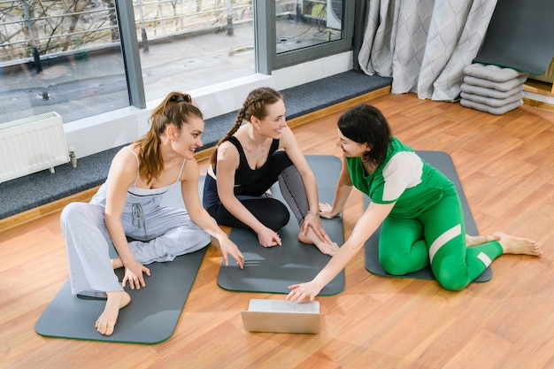 Drie sportieve meisjes zitten op matten in de fitnessstudio tijdens online yogatraining tutorials