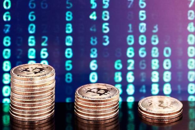 Drie stapels bitcoins met cijfers op de achtergrond