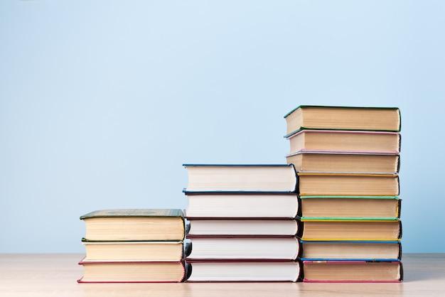Drie stapels boeken van verschillende hoogtes, staande op een houten tafel tegen een lichtblauwe muur