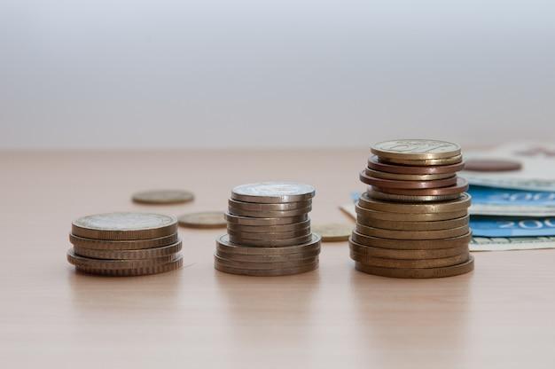 Drie stapels munten en rekeningen liggen op de tafel.