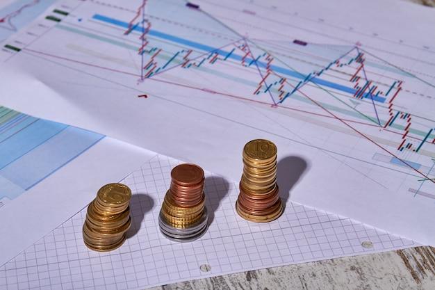 Drie stapels munten op tafel met diagrammen en papieren documenten.