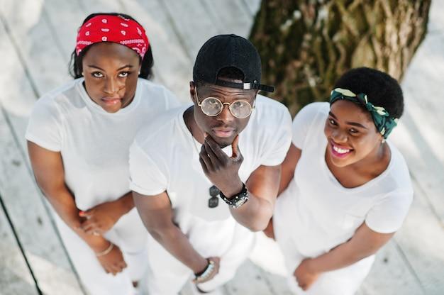 Drie stijlvolle afro-amerikaanse vrienden, draag op witte kleding. straatmode van jonge zwarte mensen. zwarte man met twee afrikaanse meisjes. uitzicht van boven.