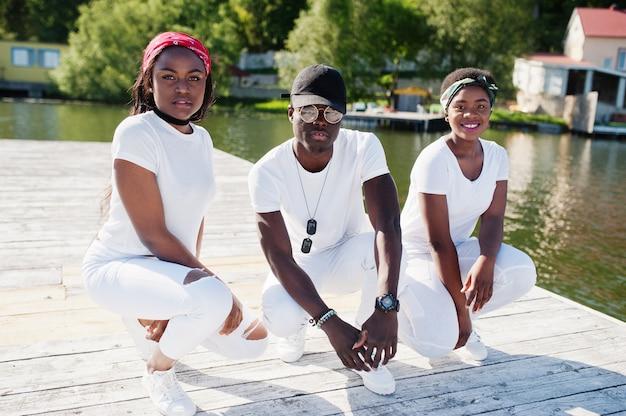Drie stijlvolle afro-amerikaanse vrienden, draag op witte kleren op pier op strand. straatmode van jonge zwarte mensen. zwarte man met twee afrikaanse meisjes.