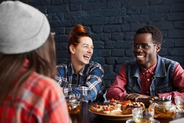 Drie stijlvolle jonge mensen die lol hebben tijdens de lunch in café, met elkaar praten en lachen om grappen