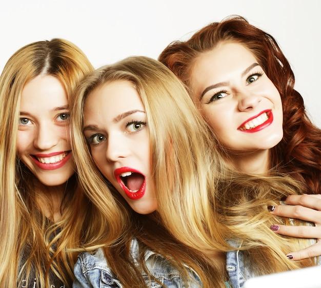 Drie stijlvolle meisjes beste vrienden die samen staan en plezier hebben