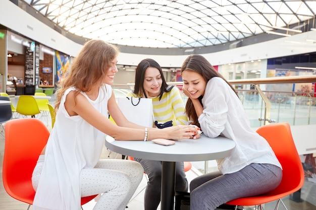 Drie stijlvolle meisjes zitten aan een tafel in een café in het moderne winkelcentrum en kletsen na het winkelen.