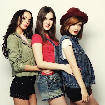 Drie stijlvolle sexy hipster meisjes beste vrienden. samen staan en plezier hebben. camera kijken. over grijze achtergrond.