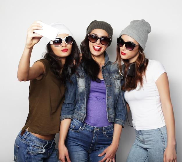 Drie stijlvolle sexy hipster meisjes beste vrienden. samen staan en plezier hebben. over grijze achtergrond.