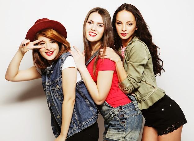 Drie stijlvolle sexy hipstermeisjes die samen staan en plezier hebben
