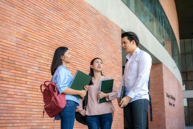 Drie studenten discussiëren over examenvoorbereiding, presentatie, studie, studie voor testvoorbereiding op de universiteit.