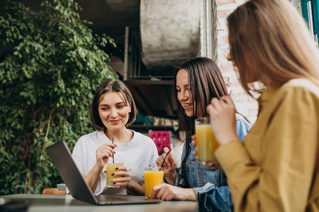 Drie studenten examen voorbereiden met laptop in een café