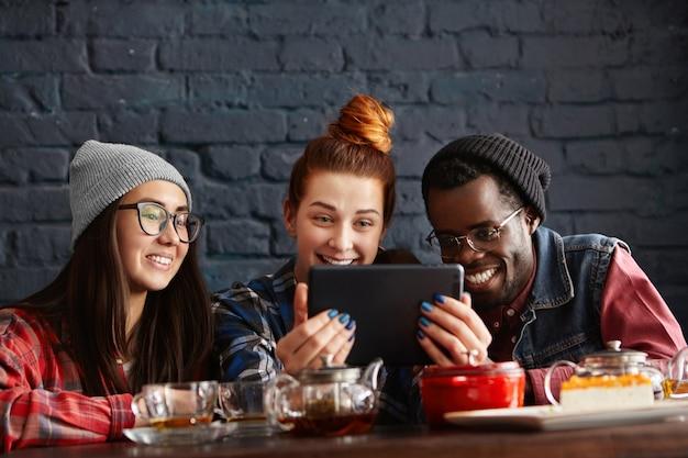 Drie studenten genieten van gratis wifi, met behulp van digitale tablet in café tijdens de lunchpauze