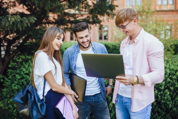 Drie studenten in stijlvolle kleding kijken naar een laptop en lachen om de universiteitscampus.