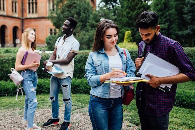 Drie studenten praten met elkaar buiten op de binnenplaats van een universiteit.
