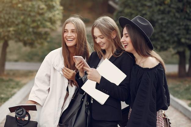 Drie studenten staan in een universiteitscampus