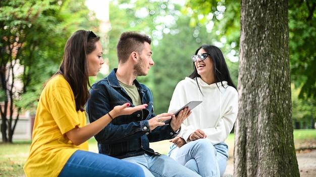 Drie studenten studeren samen met een digitale tablet zittend op een bankje buiten