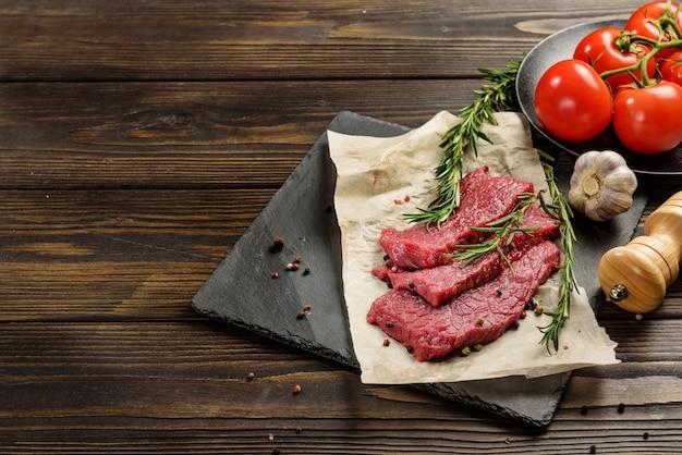 Drie stukjes rundvlees op een schaal naast de kruiden