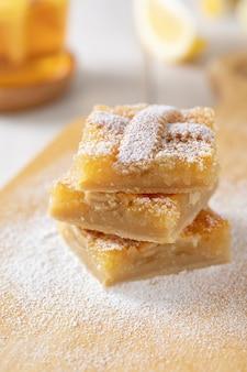 Drie stukjes zelfgemaakte zandkoek-citroentaart bestrooid met poedersuiker.