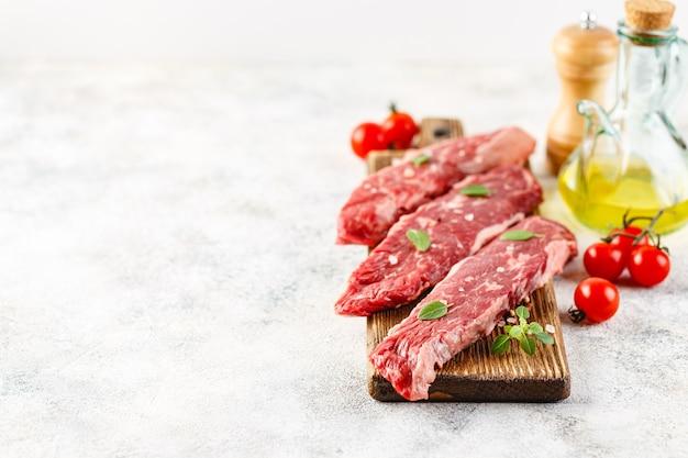 Drie stukken rauwe biefstuk op een houten snijplank, zout, peper, tomaten en olie in een fles op een licht