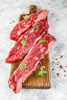 Drie stukken van rauwe biefstuk met zout op een houten snijplank, op een licht.